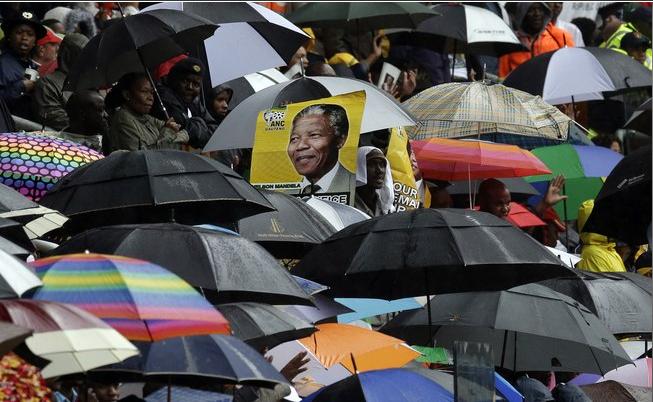 Imagem do ex-presidente Nelson Mandela, que morreu aos 95 anos, é vista. Sob chuva, milhares de sul-africanos acompanharam as cerimônias. (Foto: AP)