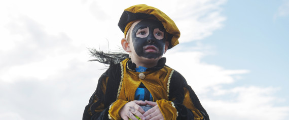 A Dutch child wearing blackface make up is carried during a demonstrate in The Hague, Netherlands on Saturday, Oct. 26, 2013, to show their determination to keep alive a tradition of allowing actors to wear blackface makeup during the country's annual St. Nicholas festival for children. A vocal minority of Dutch people, especially of African descent, and many observers in the rest of the world think the Black Pete tradition is offensive, given Pete's appearance includes curly hair, big red lips and black face-paint. But a large majority of Dutch people say Black Pete is a figure of fun and no racial insult is intended. (AP Photo/ Patrick Post)