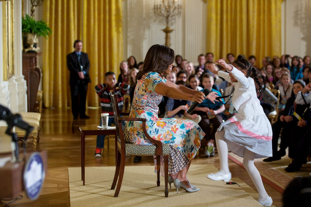 """First Lady Michelle Obama reaches out to hug a child attending the annual """"Take Our Daughters and Sons to Work Day"""" event in the East Room of the White House, April 22, 2015. (Official White House Photo by Lawrence Jackson) This official White House photograph is being made available only for publication by news organizations and/or for personal use printing by the subject(s) of the photograph. The photograph may not be manipulated in any way and may not be used in commercial or political materials, advertisements, emails, products, promotions that in any way suggests approval or endorsement of the President, the First Family, or the White House."""
