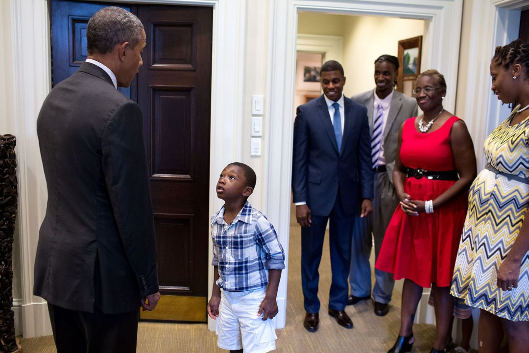 """Sept. 4, 2015 """"Four-year-old Malik Hall greets the President, almost in disbelief, before a departure photo with Malik's uncle Maurice Owens, center, and his family."""" (Official White House Photo by Pete Souza) This official White House photograph is being made available only for publication by news organizations and/or for personal use printing by the subject(s) of the photograph. The photograph may not be manipulated in any way and may not be used in commercial or political materials, advertisements, emails, products, promotions that in any way suggests approval or endorsement of the President, the First Family, or the White House."""