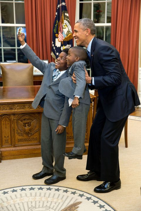 """Dec. 4, 2015 """"The President acquiesced to a selfie with 11-year-old Jacob Haynes and four-year-old James Haynes after taking a family photograph with departing White House staffer Heather Foster."""" (Official White House Photo by Pete Souza) This official White House photograph is being made available only for publication by news organizations and/or for personal use printing by the subject(s) of the photograph. The photograph may not be manipulated in any way and may not be used in commercial or political materials, advertisements, emails, products, promotions that in any way suggests approval or endorsement of the President, the First Family, or the White House."""