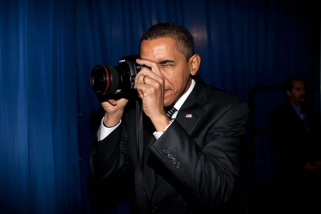 President Barack Obama takes aim with a photographer's camera backstage prior to remarks about providing mortgage payment relief for responsible homeowners. Dobson High School. Mesa, Arizona 2/18/09. Official White House Photo by Pete Souza