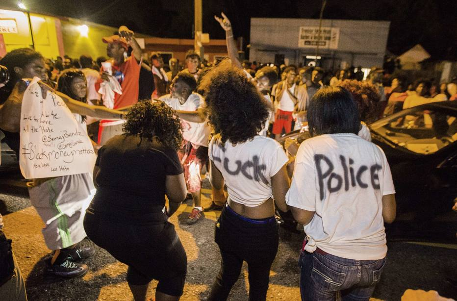 BATON ROUGE, LA -JULY 06: (EDITORS NOTE: Image contains profanity.) Protesters dance in the street near the convenience store where Alton Sterling was shot and killed, July 6, 2016 in Baton Rouge, Louisiana. Sterling was shot by a police officer in front of the Triple S Food Mart in Baton Rouge on Tuesday, July 5, leading the Department of Justice to open a civil rights investigation. Mark Wallheiser/Getty Images/AFP (Photo by Mark Wallheiser/Getty Images) == FOR NEWSPAPERS, INTERNET, TELCOS & TELEVISION USE ONLY ==
