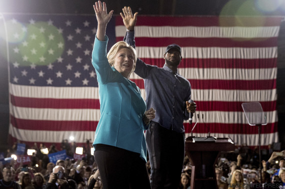 Democratic presidential candidate Hillary Clinton, left, accompanied by LeBron James, right, takes the stage at a rally at the Cleveland Public Auditorium in Cleveland, Sunday, Nov. 6, 2016. (AP Photo/Andrew Harnik)