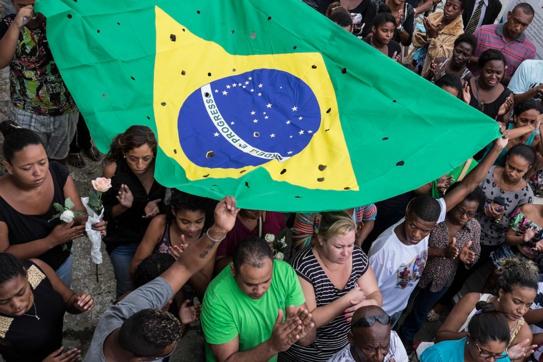Relatives and friends carry a Brazilian flag with 50 holes as they mourn Wilton Esteves Domingos Junior, 20, killed with four other friends last Satuday by policemen who shot 50 times at their car, in Rio de Janeiro, on November 30, 2015. The three policemen involved were arrested. AFP PHOTO / Christophe SIMON / AFP PHOTO / CHRISTOPHE SIMON