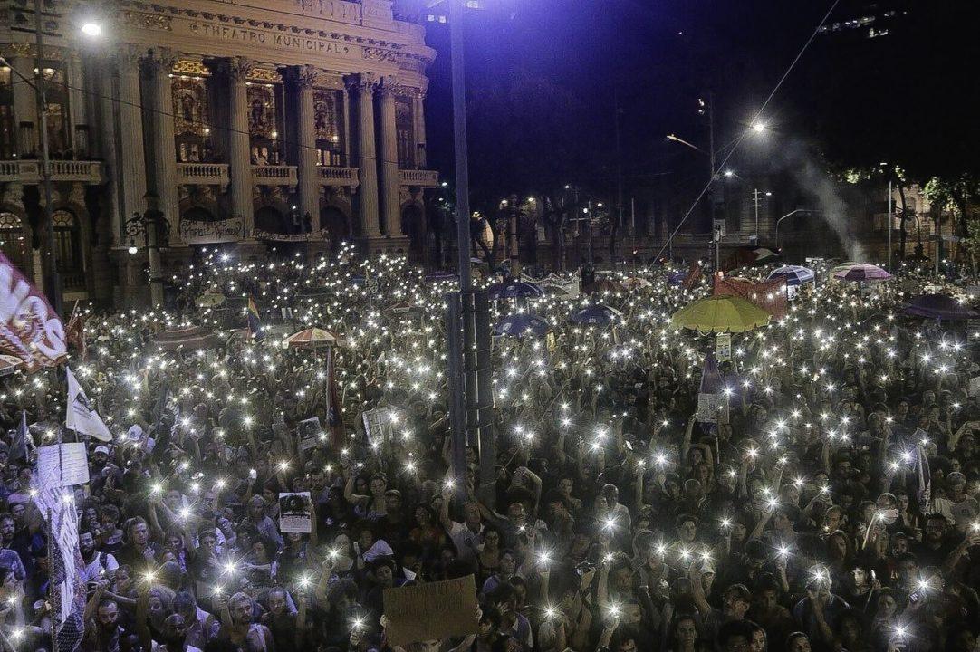 Manifestantes acendem luzes em protesto contra o assassinato de Marielle Franco e Anderson Gomes, na Cinelândia – Rio de Janeiro. (Foto: Imagem retirada do site Folha de S. Paulo)