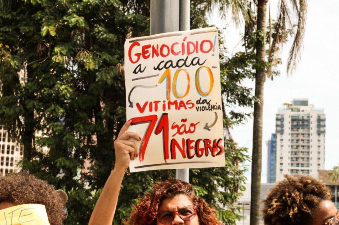 """Mulher segurando cartaz com dizeres: Genocídio: a cada 100 vitimas da violência 71 são negros"""""""