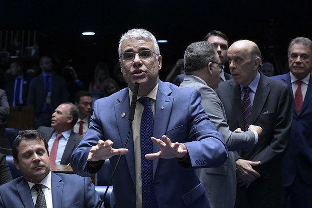 Senador Eduardo Girão, homem branco, 46 anos, de cabelos grisalhos, terno e gravata azul esccuro e camisa marrom clara. O senador está em pé, falando no microfone