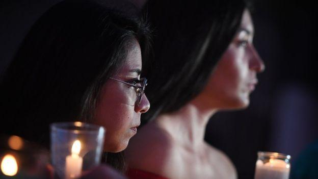 Imagem focando o rosto de duas mulheres, brancas de cabelos compridos e preto, segurando velas em suas mãos