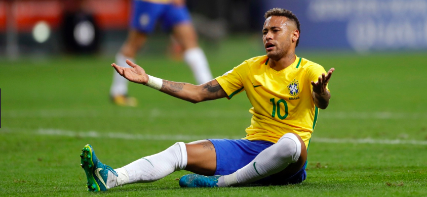 Neymar, homem negro, vestindo o uniforme da seleção brasileira, sentado no grama com as mão para cima (fazendo sinal de reclamação) durante uma partida de futebol