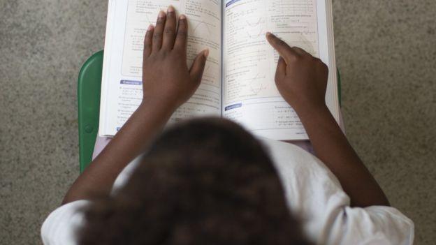 Foto d=vista de cima de uma menina lendo um livro de matemática