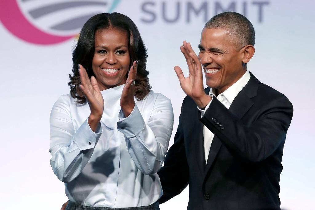 Michelle Obama- mulher negra, de cabelo liso, usando camiseta branca- e Barack Obama - homem negro, de pouco cabelo, usando terno- em pé acenando e sorrindo