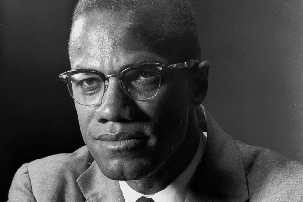 Malcolm X- homem negro, de pouco cabelo, usando óculos de grau, vestindo termo e gravata- sentado olhando para frente