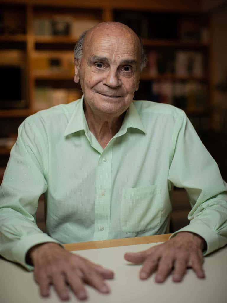 Foto de Drauzio Varella - homem branco idoso. calvo, usando camiseta de manga longa verde claro- sentado com as duas mãos em cima da mesa