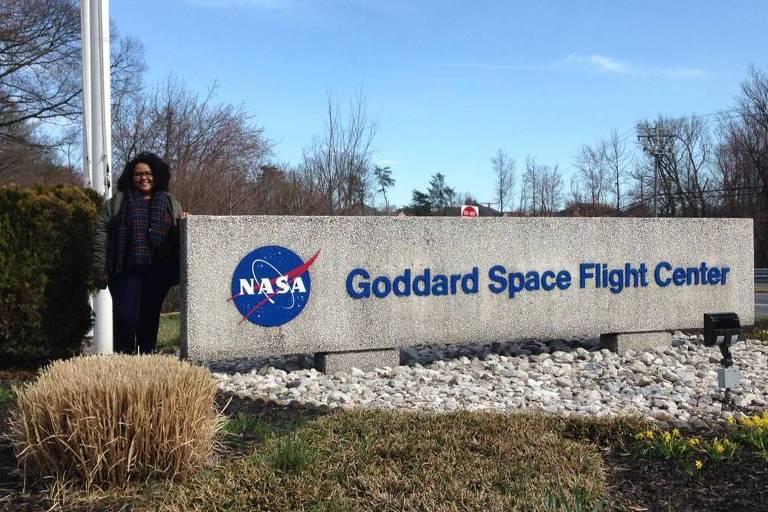 Carolyne Oliveira- mulher negra, de cabelo cacheado, usando roupas de frio- ao lado da placa do instituto da NASA