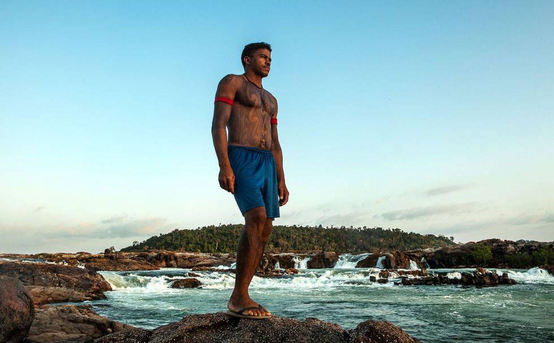 Giliard Juruna, homem indígena, sem camiseta e vestindo shorts azul escuro- em pé olhando para frente