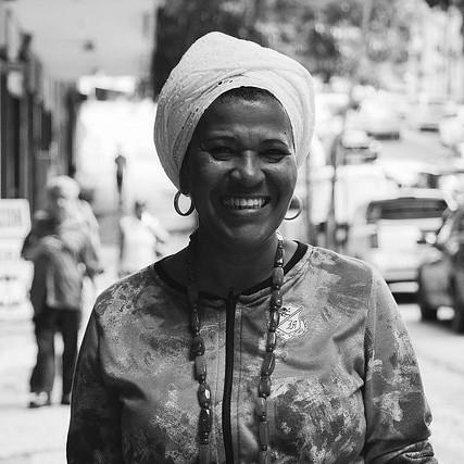 Foto em preto e branco de Makota Célia Gonçalves Souza- mulher negra, usando turbante- em pé sorrindo