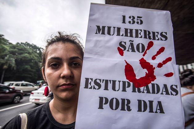 """Uma mulher- branca, de cabelo preso- segurando um cartaz escrito """"135 Mulheres são estupradas por dia"""""""