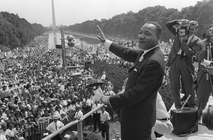 Martin Lither King Jr- homem negro, de pouco cabelo, vestindo terno e gravata- acena a seus seguidores que o acompanhava na marcha de Washington onde fez o seu mais famoso discurso 28.ago.1963
