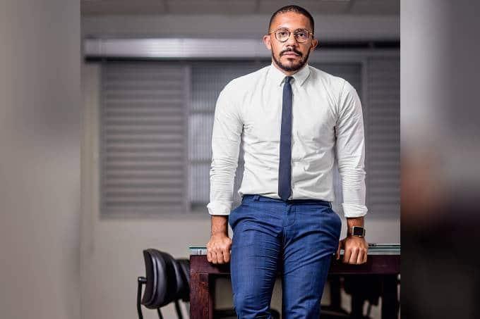 Thiago Amparo- homem negro, careca, vestindo roupa social e gravata, com um relógio no pulso esquerdo- encostado em uma mesa