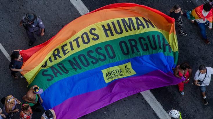"""pessoas segurando uma bandeia LGBT escrito """"Direitos Humanos são nosso Orgulho"""""""