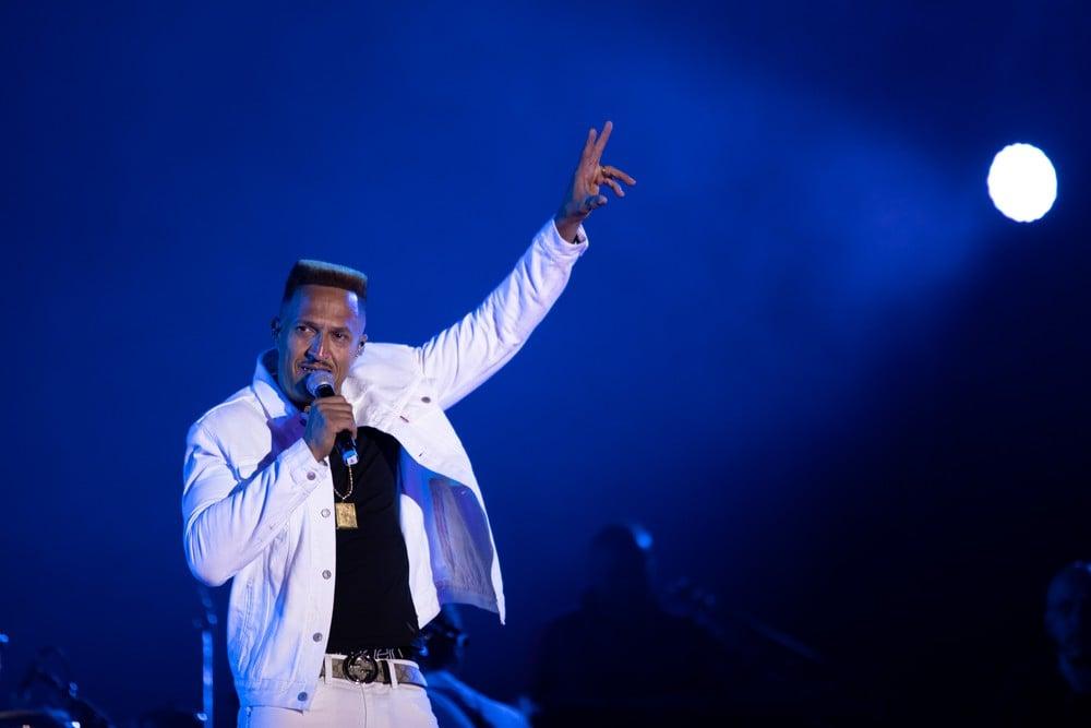 Mano Brown- homem negro, de poco cabelo e com bigode, vestindo camiseta preta e calca e jaqueta branca- com um microfone na mão direita e a mão esquerda estendida