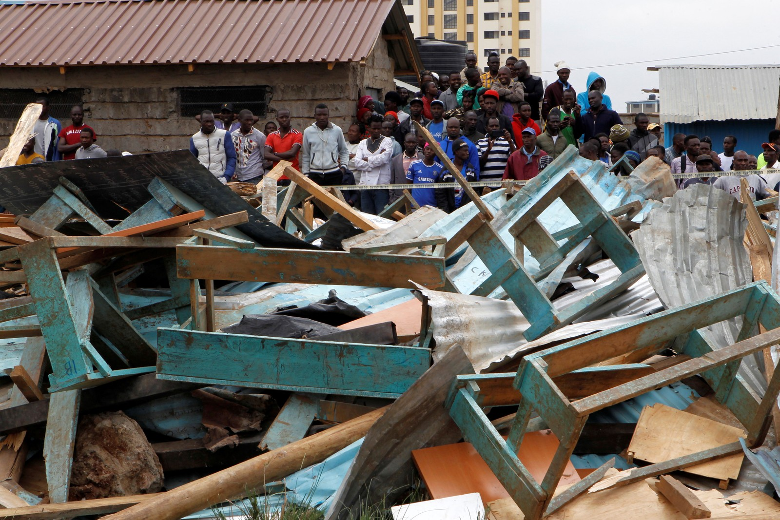 Quenianos observam sala de aula que desabou em Nairobi nesta segunda-feira (23) — Foto: Njeri Mwangi/ Reuters