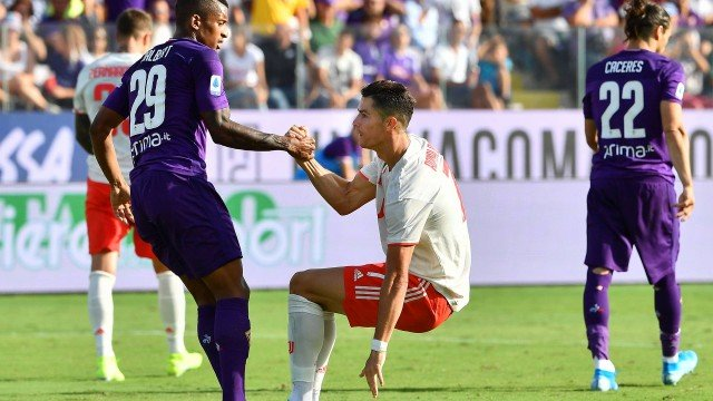 Fiorentina's Brazilian defender Dalbert (L) helps Juventus' Portuguese forward Cristiano Ronaldo get up after he fell following an overhead kick during the Italian Serie A football match Fiorentina vs Juventus on September 14, 2019 at the Artemio-Franchi stadium in Florence. (Photo by Vincenzo PINTO / AFP) Foto: VINCENZO PINTO / STF