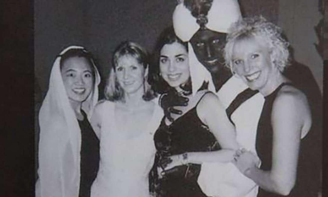 Foto em preto e branco do primeiro ministro do Canadá - homem branco realizando Blackface- rodeado por quatro mulheres