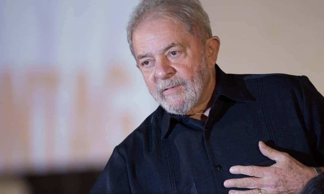 Luiz Inácio Lula da Silva- homem idoso branco, com barba e cabelos grisalhos, vestindo camisa social preta - em pé com a mãe esquerda sobre o peito