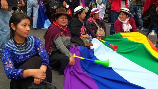Imagem de muheres sentadas no chão segurando a bandeira do Equador