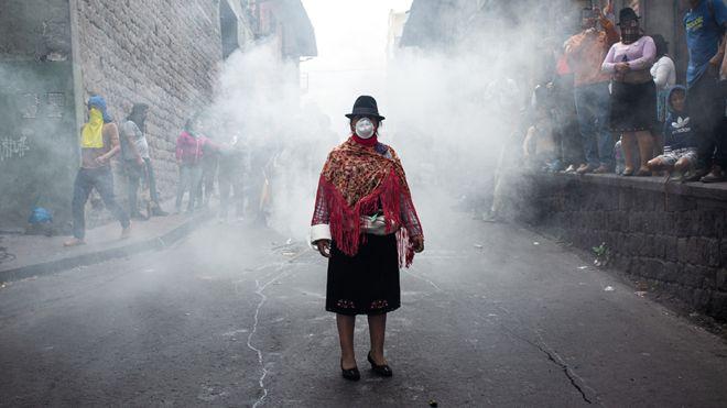 Foto de uma mulher encapusada, de pé durante o protesto