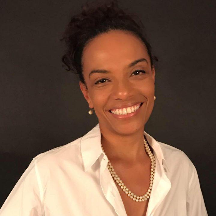 Flavia Oliveira - mulher negra, de cabelo preso, usando camiseta branca - em pé sorrindo