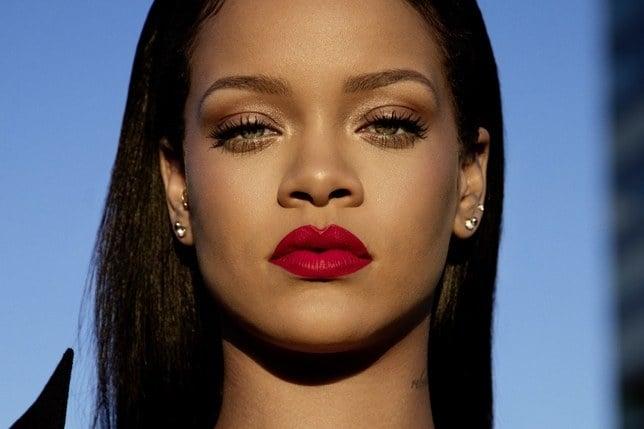 Rihanna- mulher negra, de cabelo liso preto e olhos verdes, usando batom vermelho.