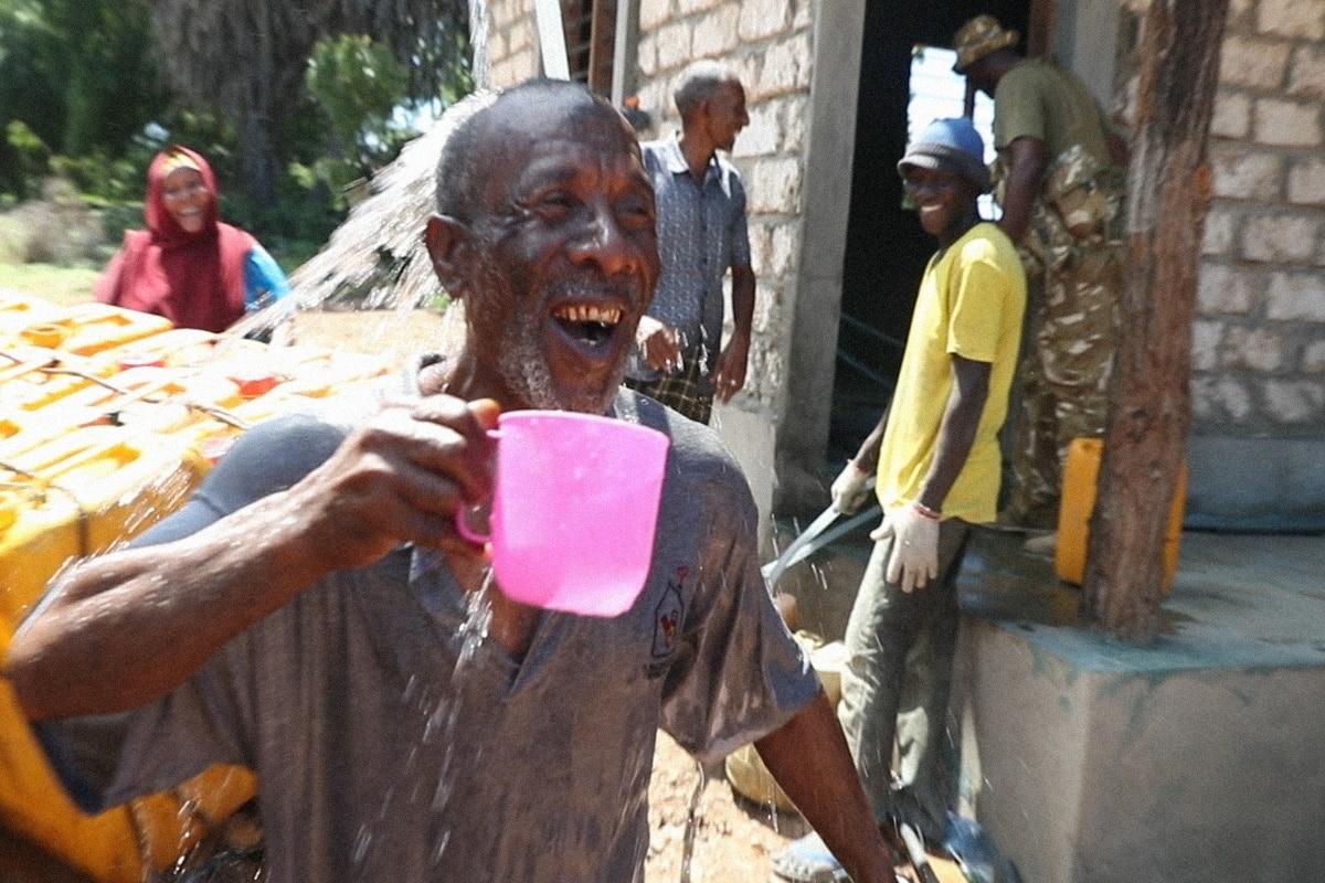 Homem- idoso negro, careca vestindo camiseta cinza- em pé sorrindo com uma caneca rosa na mão direita