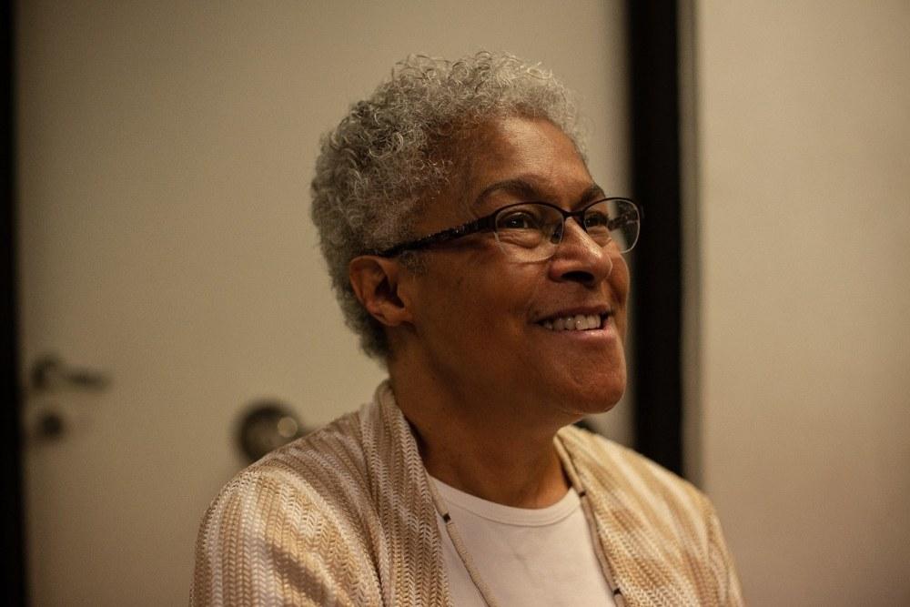 Patricia Hill Collins - mulher idosa negra, de cabelo curto e grisalho, vestindo camiseta branca e casaco marrom- sentada sorrindo