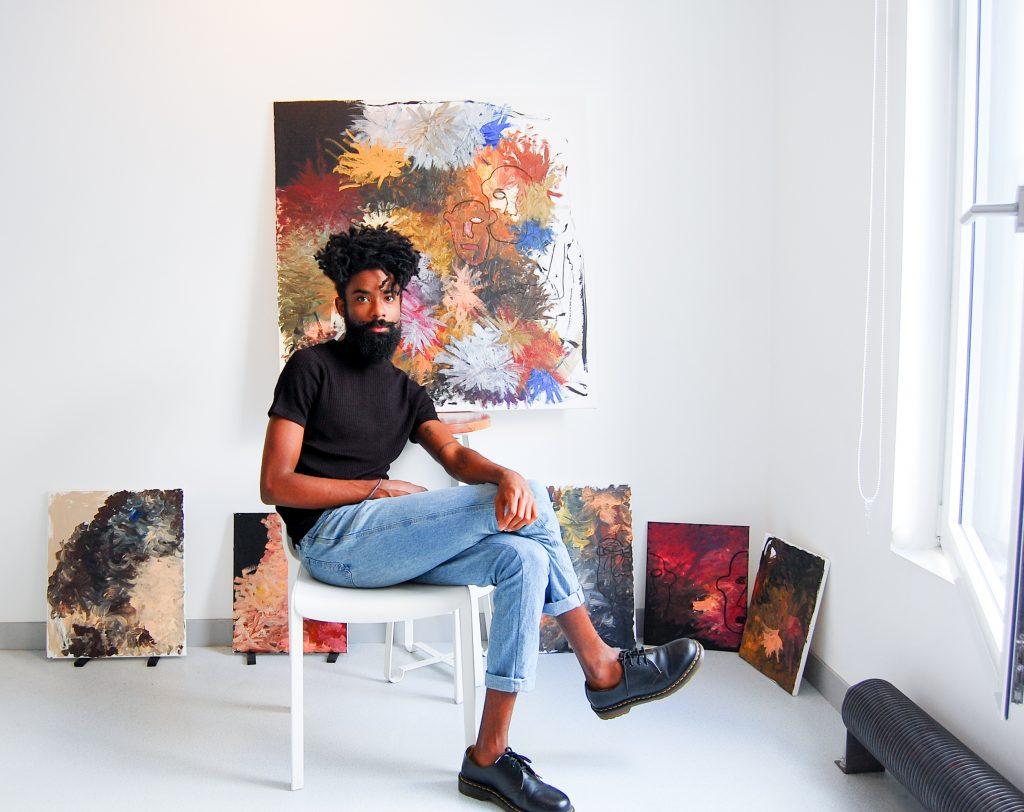 Elian Almeida- homem negro, barbudo, usando camiseta preta e calça jeans- sentado em uma cadeira cercado por seus trabalhos