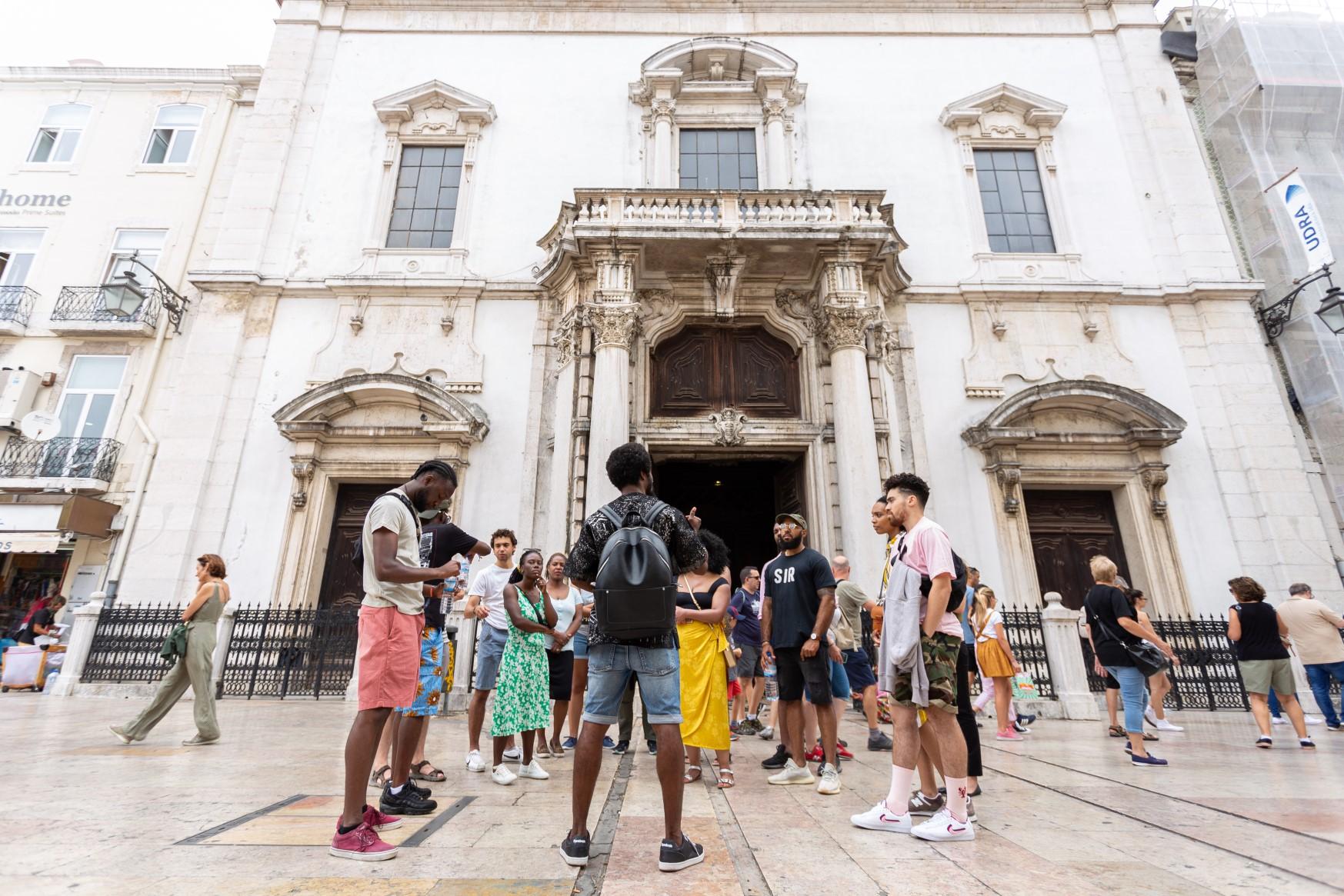 Foto de um grupo de pessoas, em sua maioria negros, em frente a um prédio antido.