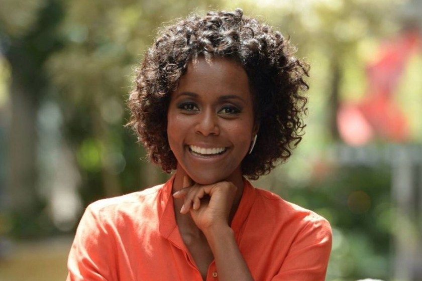 Maju Continho- mulher negra, de cabelo cacheado, usando camiseta salmão- sentada sorrindo com a mão no rosto