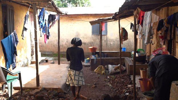 imagem de uma mulher em um quintal de barro e varias roupas penduradas no varal