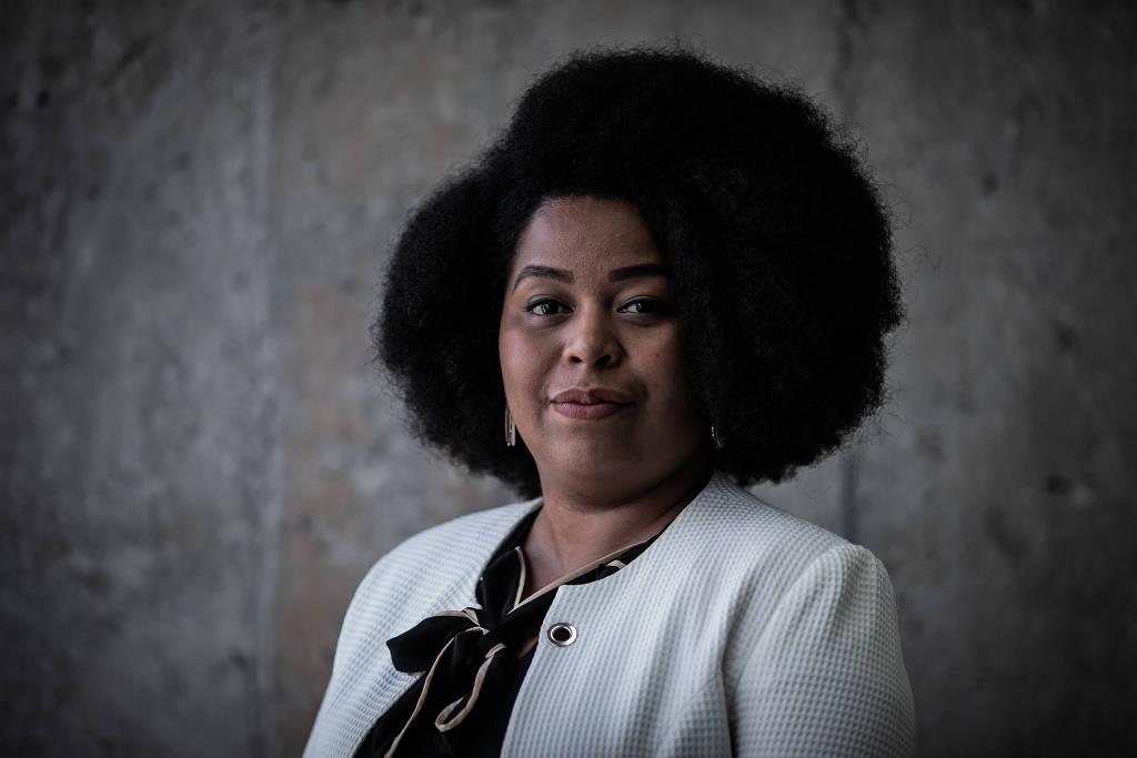 Silva Souza - mulher negra de cabelo black, usando terninho branco - em pé.
