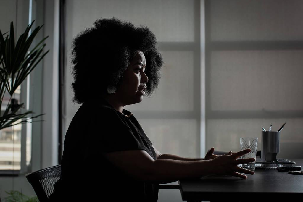 A advogada Silvia Souza- mulher negra, de cablo black power, vestindo camiseta preta- sentada em uma cadeira gesticulando