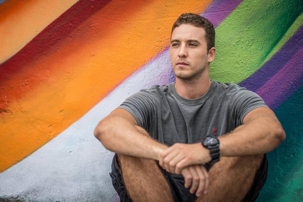 Dager Lameck,- homem branco de pouco cabelo , de camiseta cinza e bermuda preta- sentado no chão apoiando as costas em uma parede colorida