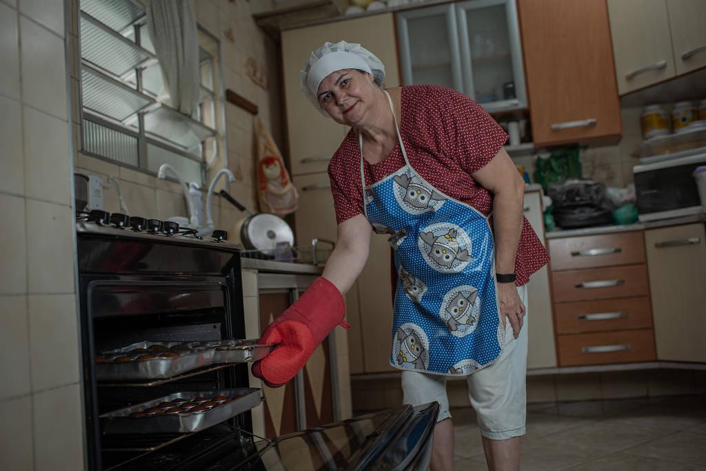 Rita Urquidi- mulher branca, usando luvas de cozinha, avental e touca - em pé tirando formas do forno