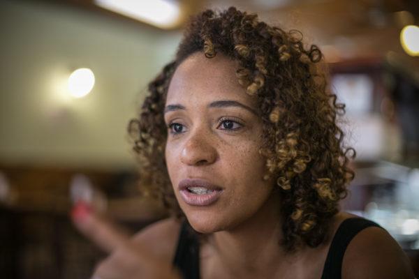 Fernanda Oliveira- mulher negra de cabelo cacheado, usando regata preta e brincos amarelo- sentada em uma cadeira e gesticulando com as mãos