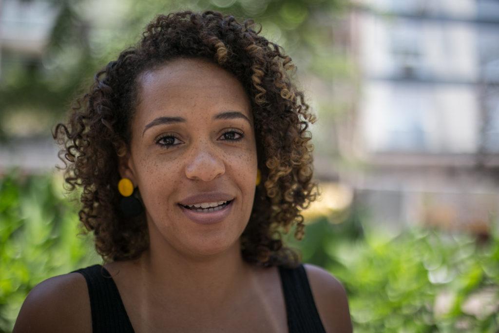 Fernanda Oliveira- mulher negra de cabelo cacheado, usando regata preta e brincos amarelo- em pé olhando para frente