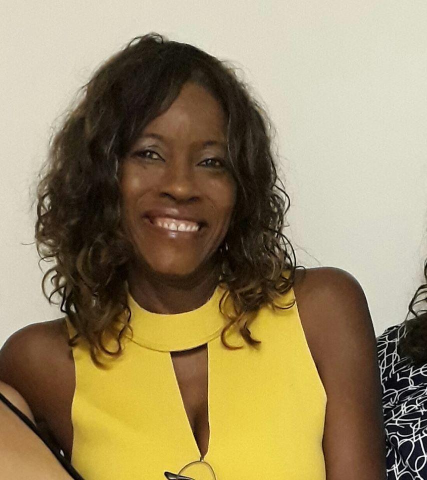 Eliane Leite - mulher negra de cabelo cacheada, vestindo camiseta amarela - em pé sorrindo.