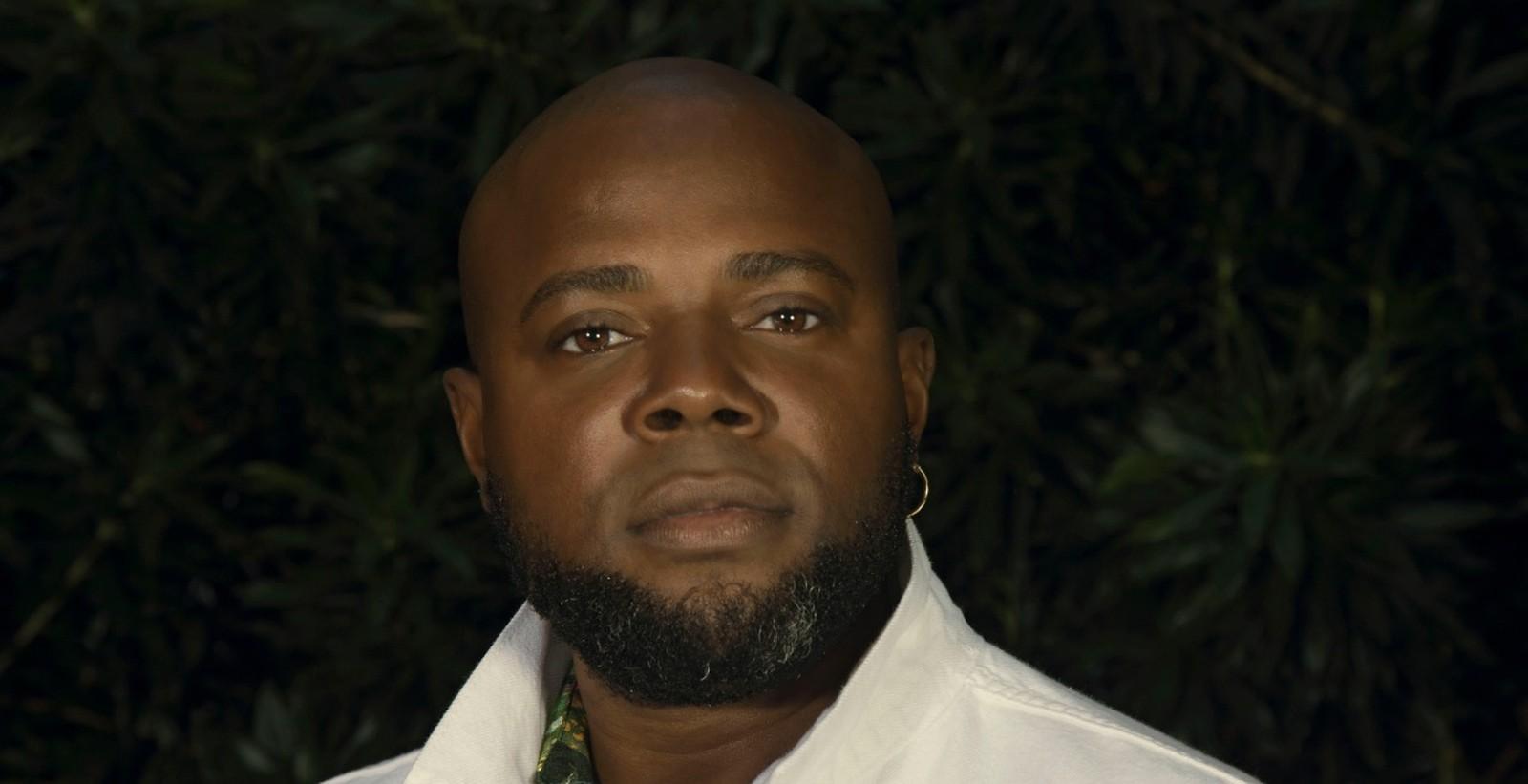 Érico Brás - homem negro, careca e de pouca barba, usando camisa branca- em pé olhando para frente
