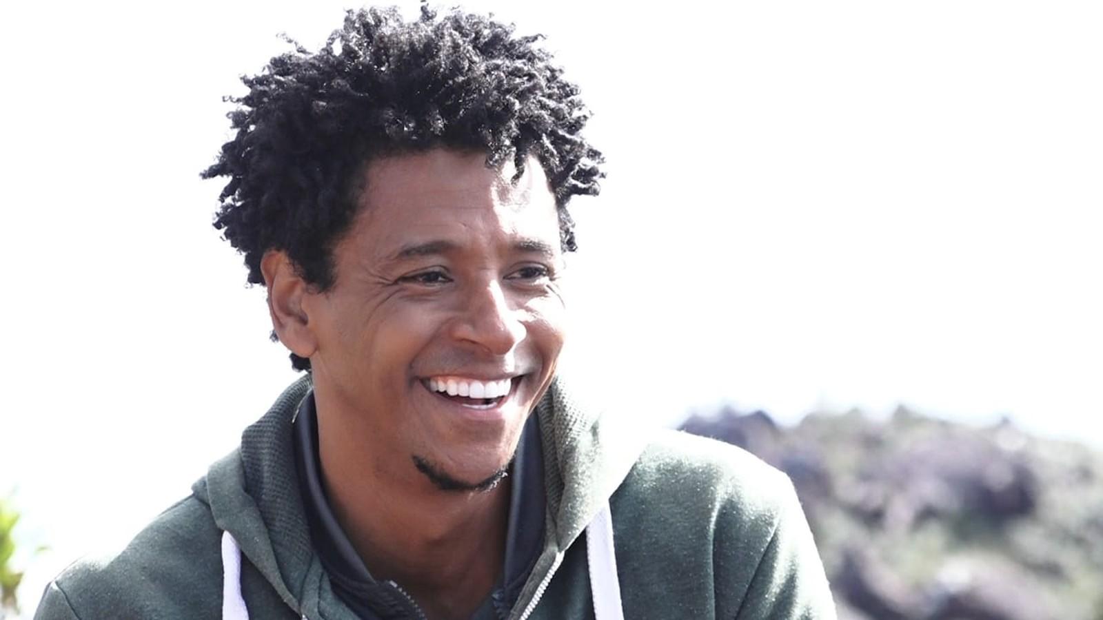 Aldri Nascimento - homem negro de cabelo crespo, usando moletom cinza- sentado ao ar livre sorrindo