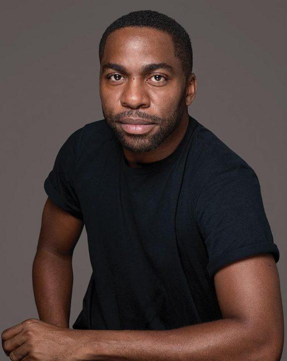 Lázaro Ramos - homem negro de pouca barba e cabelo, usando camiseta preta- sentado